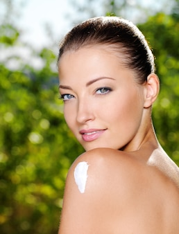 Beautiful caucasian woman with  moisturizer ceam on shoulder
