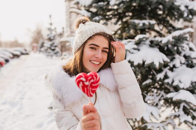 Bella donna caucasica con la caramella rossa che gode dell'inverno in vacanza. foto all'aperto della signora rilassata indossa un cappello lavorato a maglia bianco, in posa sulla strada con la neve