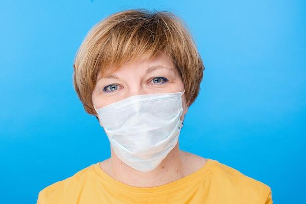 特別な医療マスクを持つ美しい白人女性は幸せです、青い背景で隔離の肖像画