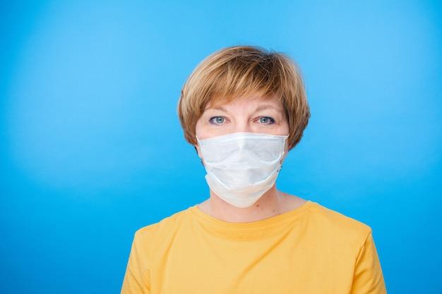 特別な医療マスク、青い背景で隔離の肖像画を持つ美しい白人女性