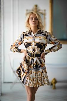 La bella donna caucasica con capelli biondi ondulati in nuovo vestito alla moda posa per la rivista di moda in appartamenti lussuosi