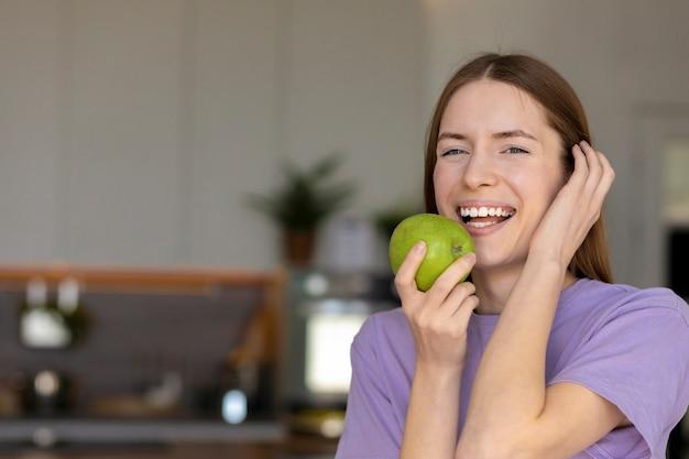 笑顔と青リンゴを食べる白い歯を持つ美しい白人女性、健康的なライフスタイル