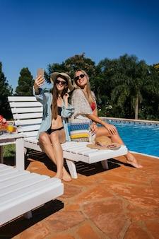 プールの近くで自分撮りをしている美しい白人女性