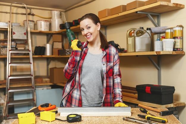 格子縞のシャツと灰色のtシャツを着た美しい白人の若い茶色の髪の女性は、テーブルの場所で大工のワークショップで働いて、家具を作りながら鉄と木片にドリル穴を開けます。