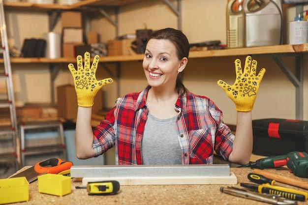 Красивая кавказская молодая женщина с каштановыми волосами в клетчатой рубашке, серой футболке, желтых перчатках, разводящих руки, работает в столярной мастерской за деревянным столом с куском железа и дерева, различными инструментами