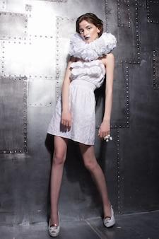 金属の壁に奇妙な襟付きの白いドレスでポーズをとる美しい白人の若い贅沢な女性。