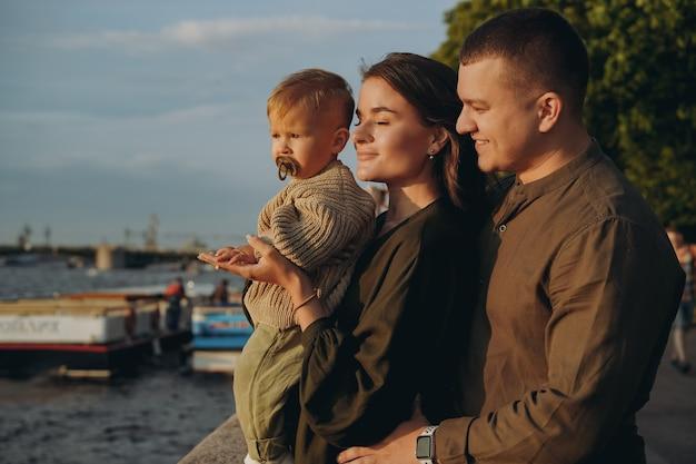 러시아 상트페테르부르크 시 부두에서 아기 아들을 안고 있는 아름다운 백인 젊은 가족 부부. 고품질 사진