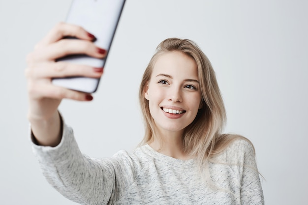 Beautiful caucasian young female with long blonde dyed hair and appealing dark eyes holding mobile phone, posing for selfie