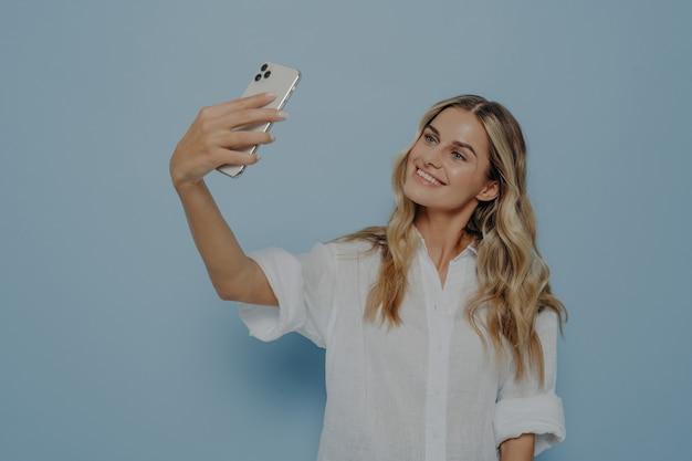 携帯電話を持って自分撮りのポーズをとって、軽薄な笑顔で画面を見て、魅力的な女性がオンラインでソーシャルネットワークの写真を作っている長いブロンドの染めた髪を持つ美しい白人の若い女性