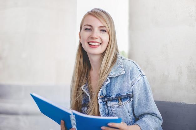 Студент красивая кавказская молодая девушка с ноутбуком, сидя на полу возле университета