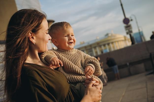 러시아 상트페테르부르크 시 부두에서 아기 아들을 안고 있는 아름다운 백인 젊은 엄마. 고품질 사진