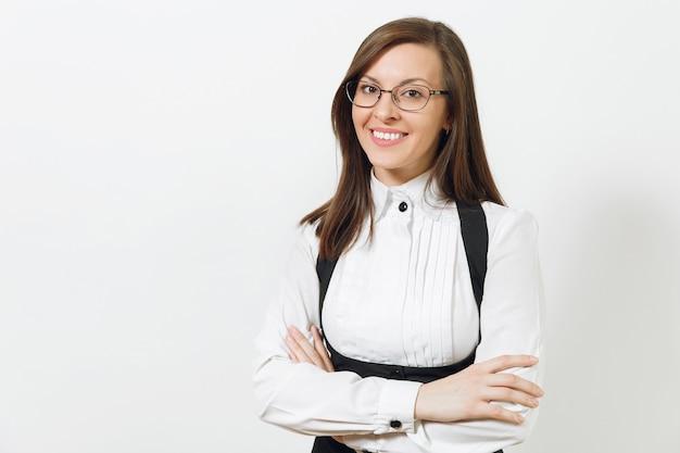 Bella giovane caucasica sorridente donna d'affari dai capelli castani in abito nero, camicia bianca e occhiali che si tengono per mano incrociati isolati su sfondo bianco. dirigente o lavoratore. copia spazio per la pubblicità.