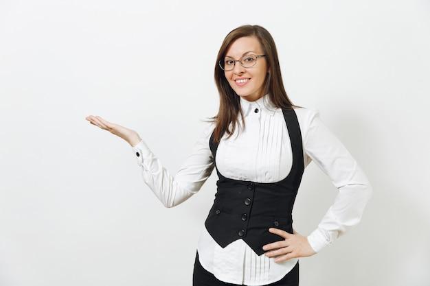 Bella giovane caucasica sorridente donna d'affari dai capelli castani in abito nero, camicia bianca e occhiali che puntano la mano da parte isolata su sfondo bianco. dirigente o lavoratore. copia spazio per la pubblicità.