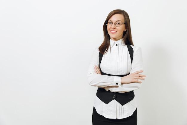 Красивая кавказская молодая улыбающаяся каштановая бизнес-леди в черном костюме, белой рубашке и очках, взявшись за руки, пересекла изолированные на белом фоне. менеджер или рабочий. скопируйте место для рекламы.
