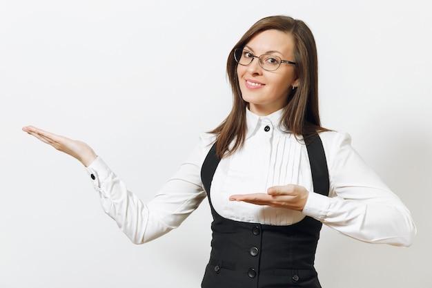 Красивая кавказская молодая улыбающаяся каштановая деловая женщина в черном костюме, белой рубашке и очках, указывая руками в сторону, изолирована на белой стене