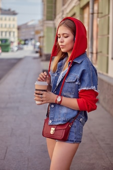 Beautiful caucasian young woman about 25 years old in red hoodie and with long blond hair is walking in center of saint petersburg and drinking coffee from paper cup.