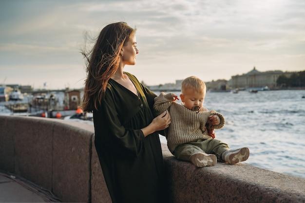 러시아 상트페테르부르크 시 부두에서 아기 아들을 안고 있는 아름다운 백인 젊은 여성 부부. 고품질 사진