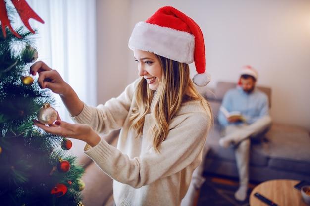 セーターとリビングルームに立っている間クリスマスツリーを飾る頭の上のサンタさんの帽子に身を包んだ美しい白人の若い女性。バックグラウンドで彼女のボーイフレンドは本を読んでいます。