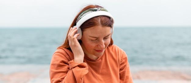Красивая кавказская молодая женщина слушает музыку в наушниках в солнечный день во время прогулки у океана