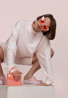スタジオでピンクのアクセサリーとピンクのスポーツ衣装でポーズをとる美しい白人の若い女性
