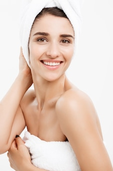 Beautiful caucasian young woman with bath towel on head covering her breasts, on white touching her skin.