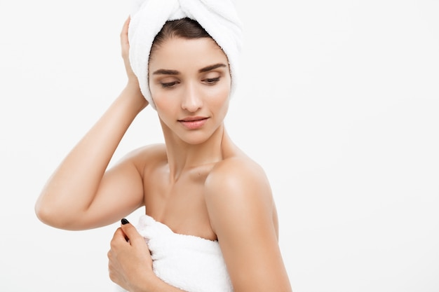 Beautiful caucasian young woman with bath towel on head covering her breasts, on white