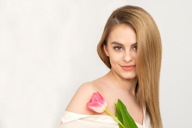 흰색 배경에 대해 하나의 튤립과 아름 다운 백인 젊은 여자