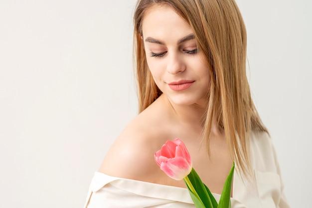 흰색 배경에 대해 꽃을 찾고 하나의 튤립과 아름 다운 백인 젊은 여자