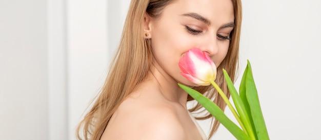 흰 벽에 꽃을 찾고 하나의 튤립과 아름 다운 백인 젊은 여자