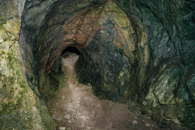 美しい洞窟。暗いダンジョンの中からの眺め。洞窟のテクスチャ壁。洞窟の中の湿気。トンネルの終わりに光。