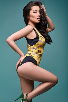 Beautiful charming asian girl in colorful swimsuit on a bright