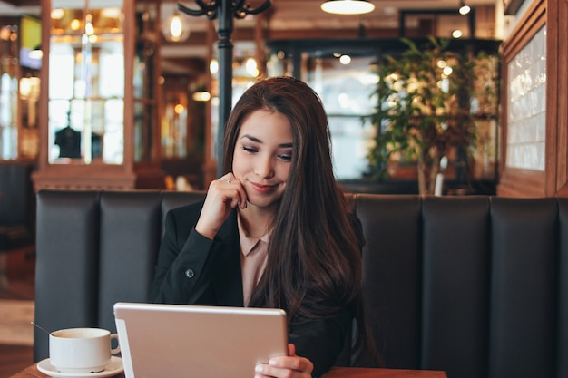 Beautiful charming brunette smiling asian girl with tablet at table in cafe