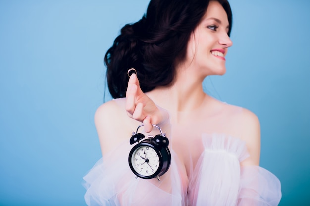 Beautiful charming girl in white wedding dress, being late in morning, and holding in her hand retro alarm clock and ring