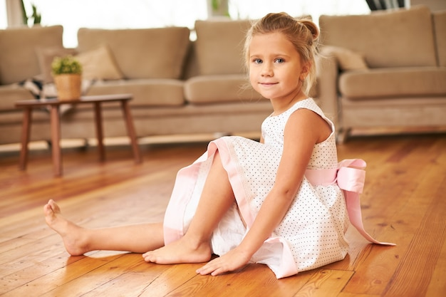 Beautiful charming little girl wearing festive dress with full skirt sitting barefooted on kitchen floor