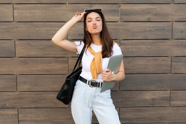 Красивая очаровательная молодая брюнетка женщина смотрит в камеру, держа компьютерный ноутбук и солнцезащитные очки
