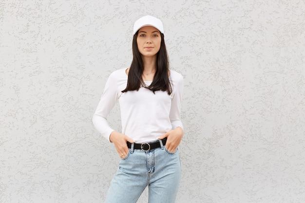 Красивая очаровательная молодая европейская женщина позирует у белой стены