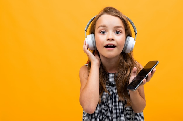 白い壁に白いヘッドフォンでカジュアルな表情で美しい魅力的な若い女の子