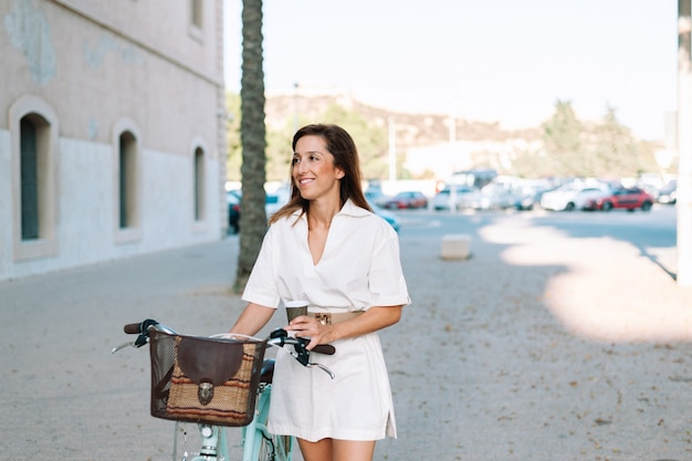 Beautiful and cheerful adult young woman enjoy bike ride in sunny urban outdoor leisure activity