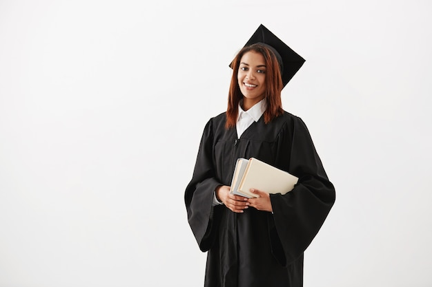 Beautiful cheerful african female graduate smiling holding books. copy space.
