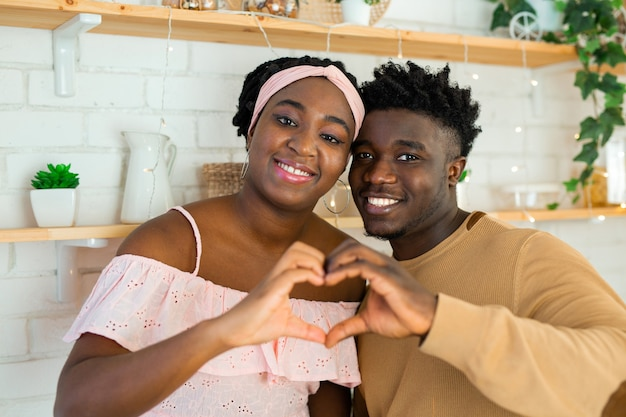 Beautiful and cheerful african man and woman in the kitchen together with heart hand gesture