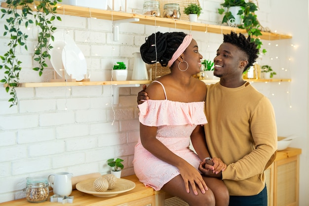 Beautiful and cheerful african man and woman in the kitchen together