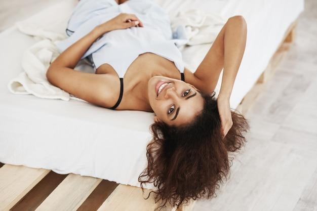 Bella donna africana allegra nella menzogne sorridente degli indumenti da notte sul letto a casa.