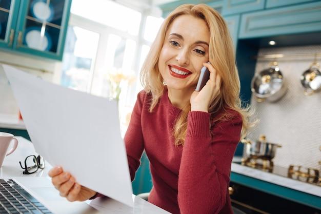 彼女のラップトップに座っている間、笑顔で一枚の紙を持って電話で話している美しい陽気な金髪の若い女性