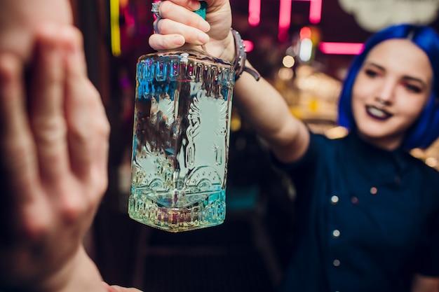 Красивая жизнерадостная брюнетка-бармен девушка в белой рубашке и черном галстуке-бабочке, подает алкогольный напиток в баре ночного клуба, держит бутылку в руке, наливает напиток в бокал