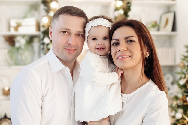 Beautiful cheerful caucasian family of mother, father and cute baby girl in white clothes smiling at camera.