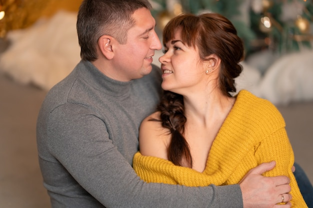 美しい陽気なカップルが居心地の良い家庭的な雰囲気の中でクリスマス休暇を迎えます
