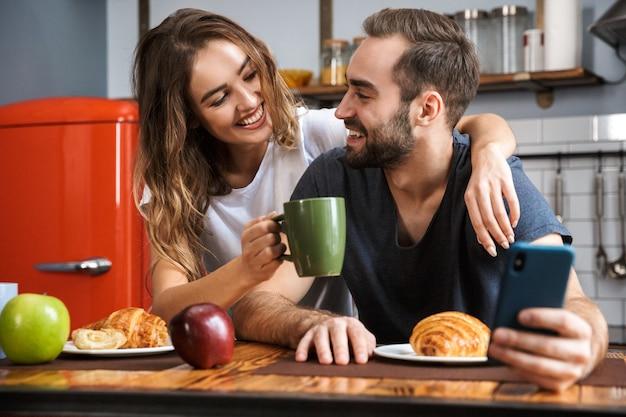 Красивая веселая пара завтракает на кухне, используя мобильный телефон