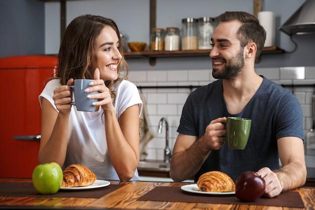 Красивая веселая пара завтракает на кухне