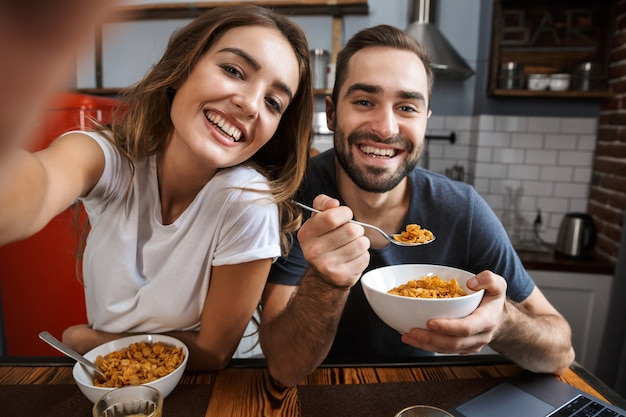 Beautiful cheerful couple having breakfast at the kitchen, taking a selfie