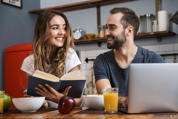 Beautiful cheerful couple having breakfast at the kitchen, using laptop computer, reading a book